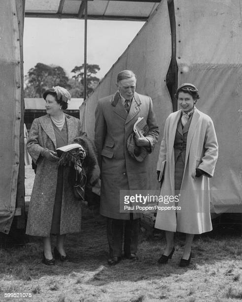 Queen Elizabeth II and Queen Elizabeth the Queen Mother stand with the Henry Somerset 10th Duke of Beaufort Master of the Queen's Horse after...