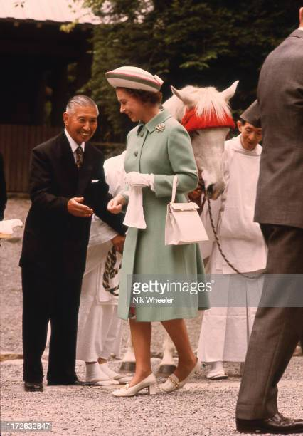 Queen Elizabeth II and sacred white horse at Ise Grand Shrine, a Shinto Temple, during her tour of Japan in 1975