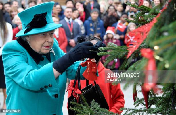 Queen Elizabeth II and Shylah Gordon, aged 8, attach a bauble to a Christmas tree during the opening of the Queen Elizabeth II centre at CORAM on...