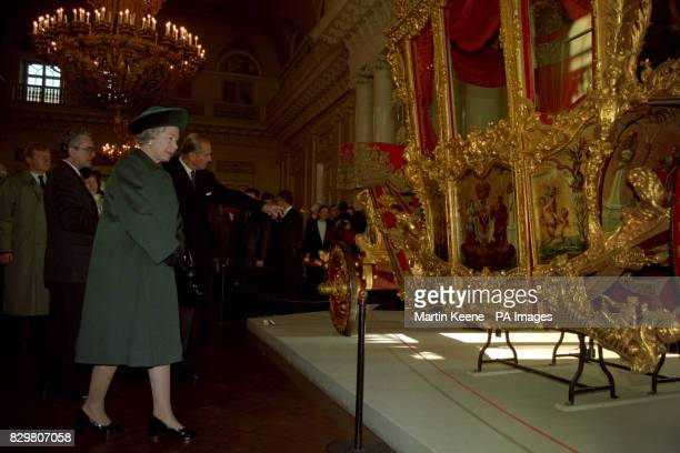 Queen Elizabeth II and the Duke of Edinburgh admire an 18th century carriage used by Peter the Great and Catherine the Great during a visit to the...
