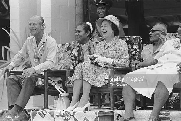 Queen Elizabeth II and the Duke of Edinburgh enjoy an organised spectacle during their visit to the Pacific island of Tuvalu October 1982