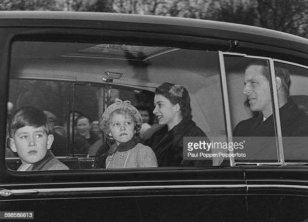 Queen Elizabeth II and the Duke of Edinburgh pictured together in the back of a car with their children Princess Anne and Prince Charles as the royal...