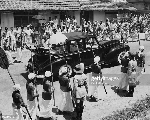 Queen Elizabeth II and the Duke of Edinburgh riding in the back of an open car under an umbrella driving through the crowded streets on their way to...