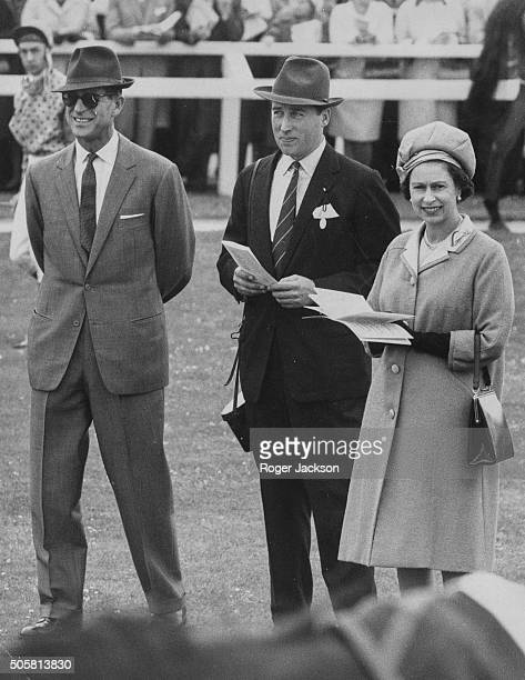 Queen Elizabeth II and the Duke of Edinburgh talking to racing manager Lord Porchester or Henry Herbert at Newbury Races England September 30th 1969