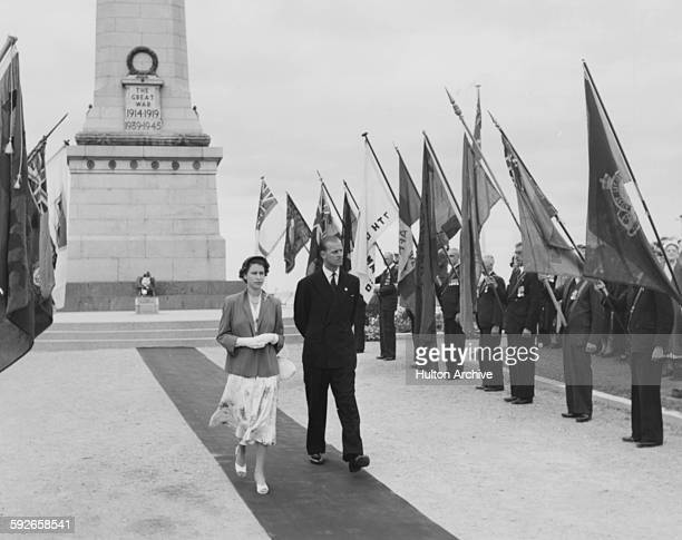 Queen Elizabeth II and the Duke of Edinburgh walking past the standards of the exservicemen's associations after laying a wreath on the war memorial...