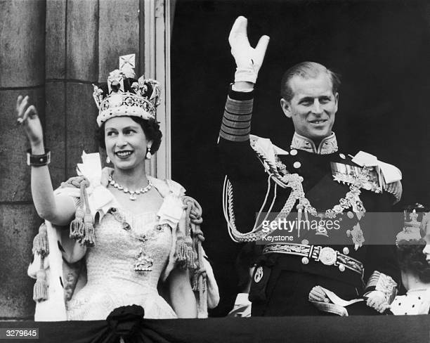 Queen Elizabeth II and the Duke of Edinburgh wave at the crowds from the balcony at Buckingham Palace after Elizabeth's coronation, 2nd June 1953.