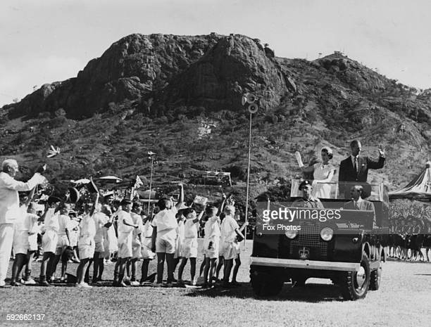 Queen Elizabeth II and the Duke of Edinburgh waving from the back of their Land Rover to a group of youngsters as they arrive at the Children's...