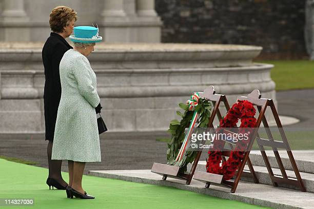 Queen Elizabeth II and the Irish President Mary McAleese observe a minute's silence after laying wreaths at the Irish War Memorial Garden in...