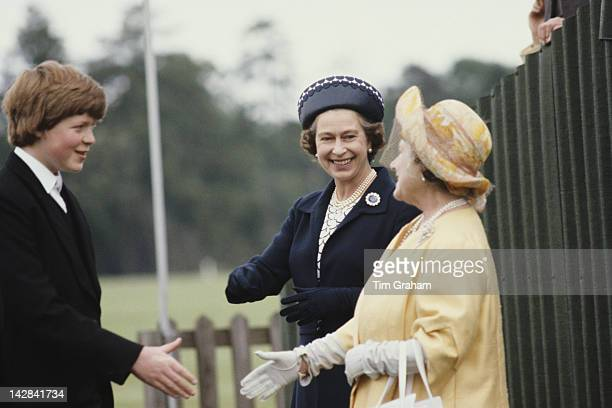 Queen Elizabeth II and the Queen Mother shake hands with Viscount Althorp later the 9th Earl Spencer during the Eton Boys' Tea Party at Windsor 21st...