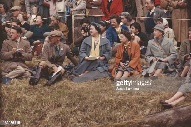 Queen Elizabeth II and the Queen Mother sitting on the ground to watch the Badminton Horse Trials 1956 On the Queen's other side is Mary Countess of...