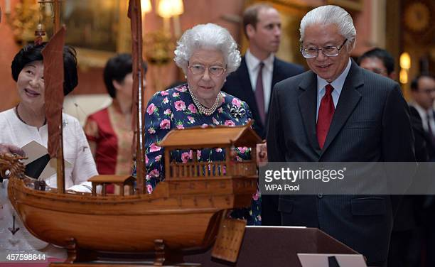 Queen Elizabeth II and the Singapore President Tony Tan Keng Yam view a display of Singaporean items from the Royal Collection at Buckingham Palace...
