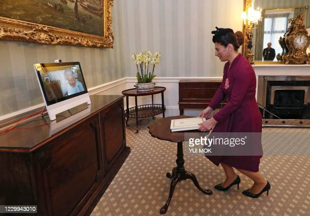 Queen Elizabeth II appears on a screen by videolink from Windsor Castle, during a virtual audience to receive Her Excellency Sophie Katsarava , the...