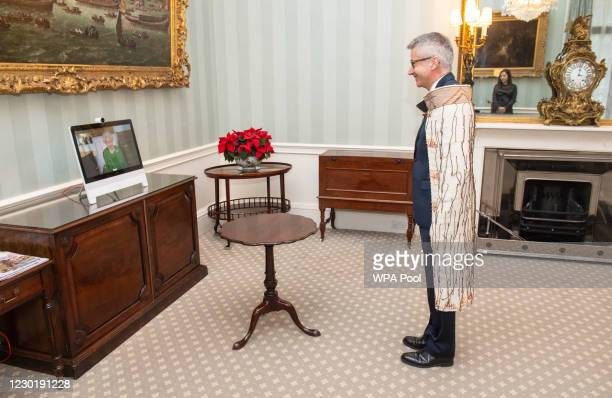 Queen Elizabeth II appears on a screen by videolink from Windsor Castle, where she is in residence, during a virtual audience to receive the High...