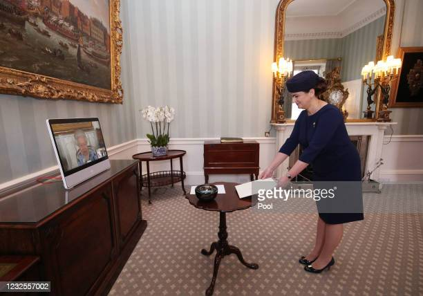 Queen Elizabeth II appears on a screen by videolink from Windsor Castle, where she is in residence, during a virtual audience to receive Her...