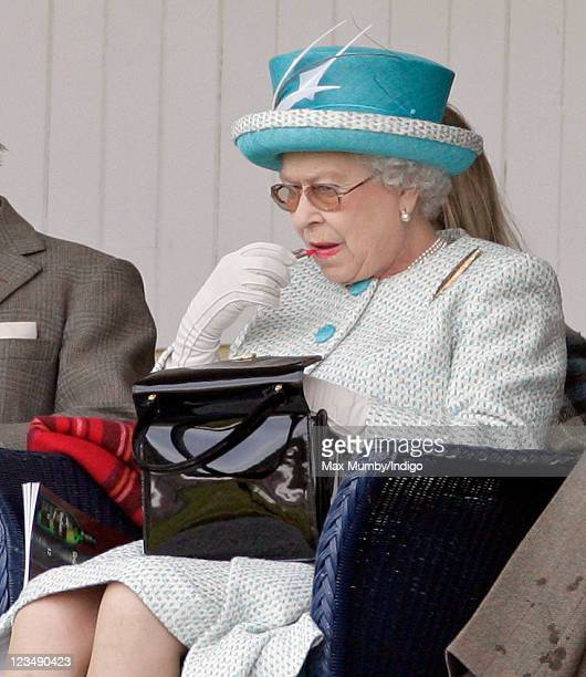 Queen Elizabeth II applies her lipstick as she attends the annual Braemar Gathering and Highland Games at The Princess Royal and Duke of Fife...