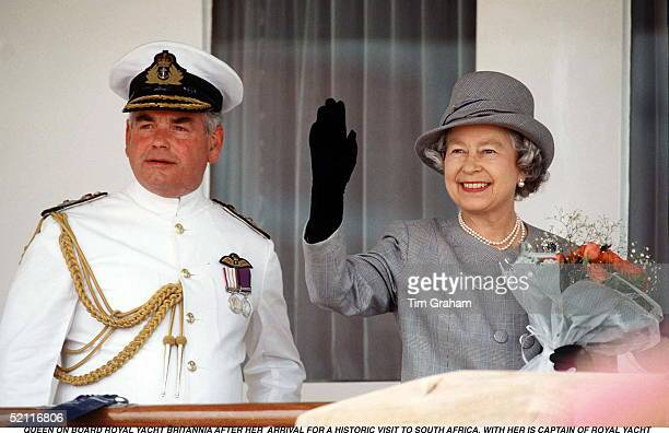 Queen Elizabeth II Arrives On Board Royal Yacht Britannia Waving To Crowds With The Then Captain Of Hmy Britannia Escorting Her. Simonstown Naval...