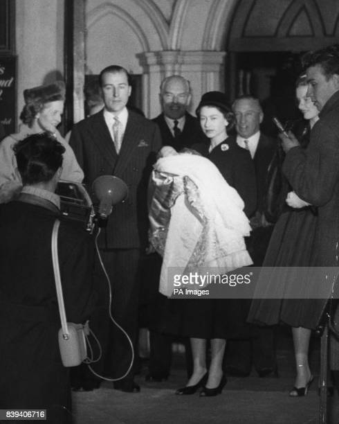 Queen Elizabeth II as godmother holds the baby George Herbert son of her childhood friend Lord Porchester at left after the christening at St Paul's...