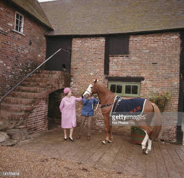 Queen Elizabeth II at Rye in Sussex, with racehorse Augustine, which used to belong to her, 28th October 1966.