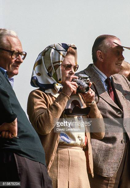 Queen Elizabeth II at the Royal Windsor Horse Show takes a photo on her Leica M3 camera while watching her husband compete on May 15 1982