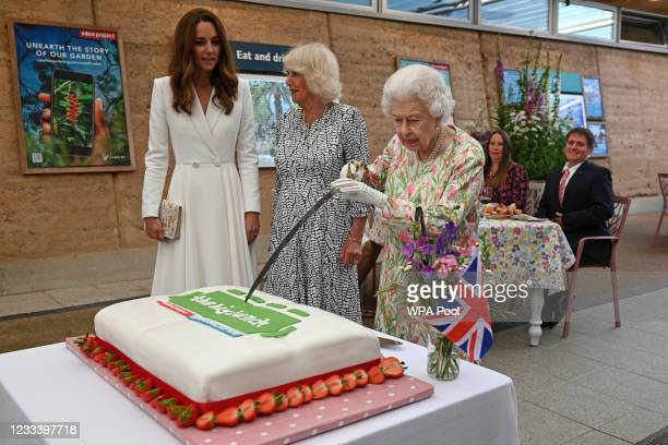 Queen Elizabeth II attempts to cut a cake with a sword, lent to her by The Lord-Lieutenant of Cornwall, Edward Bolitho, to celebrate of The Big Lunch...