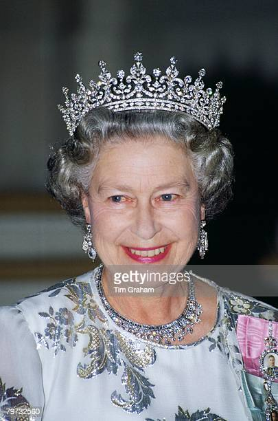 Queen Elizabeth II attends a banquet in Paris wearing a white evening dress embroidered with silver by designer Ian Thomas, the Queen Mary's Girls of...