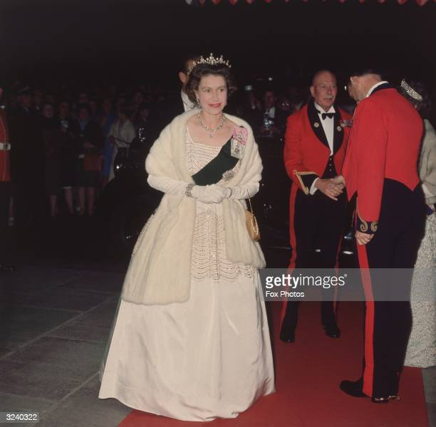 Queen Elizabeth II attends a film premiere wearing a white beaded evening gown by designer Norman Hartnell