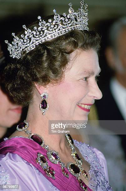 Queen Elizabeth II attends a State Banquet in Portugal wearing the Crown Amethyst Suite of Jewels which originally belonged to Queen Victoria's...