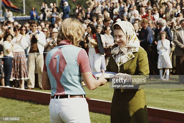 Queen Elizabeth II awards a plate to a player at a polo match 1981