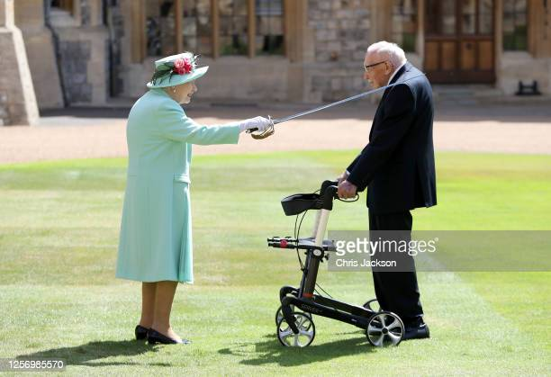 Queen Elizabeth II awards Captain Sir Thomas Moore with the insignia of Knight Bachelor at Windsor Castle on July 17, 2020 in Windsor, England....