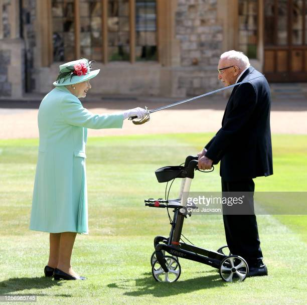 Queen Elizabeth II awards Captain Sir Thomas Moore with the insignia of Knight Bachelor at Windsor Castle on July 17 2020 in Windsor England British...