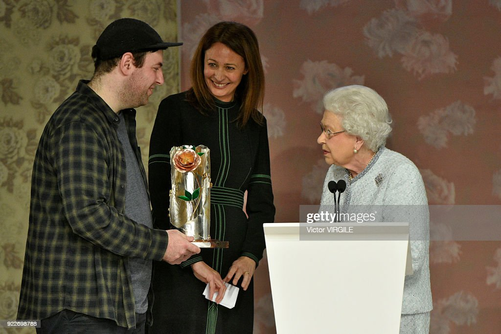 Queen Elizabeth II (R) awards designer Richard Quinn (L) the inaugural Queen Elizabeth II award for British Design alongside Chief Executive of the British Fashion Council Caroline Rush (C) during London Fashion Week February 2018 on February 20, 2018 in London, England.