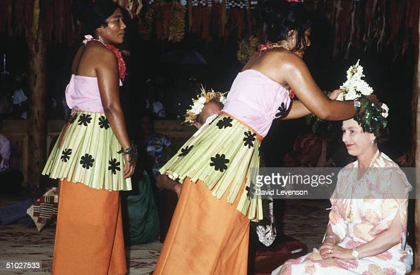 Queen Elizabeth II being crowned with a head dress of frangipani flowers Queen Elizabeth II was at a traditional feast of local produce at the Vaiaku...