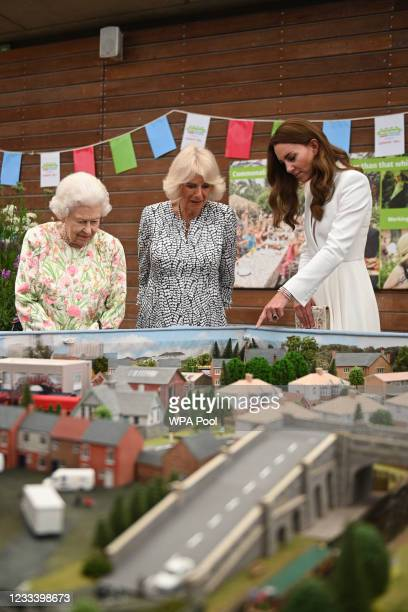 Queen Elizabeth II , Camilla, Duchess of Cornwall and Catherine, Duchess of Cambridge look at a scale model of Big Lunch events that have been held...