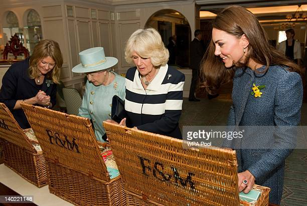 Queen Elizabeth II Camilla Duchess Of Cornwall and Catherine Duchess of Cambridge look inside their hampers filled with gifts while visiting Fortnum...