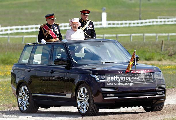 Queen Elizabeth II CaptainGeneral of The Royal Regiment of Artillery stands in the State Review Range Rover to inspect an Armoured Parade as she...