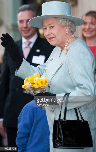 Queen Elizabeth II carrying posy of daffodils given to her by a wellwisher on St David's Day waves as she departs Fortnum Mason store on March 1 2012...