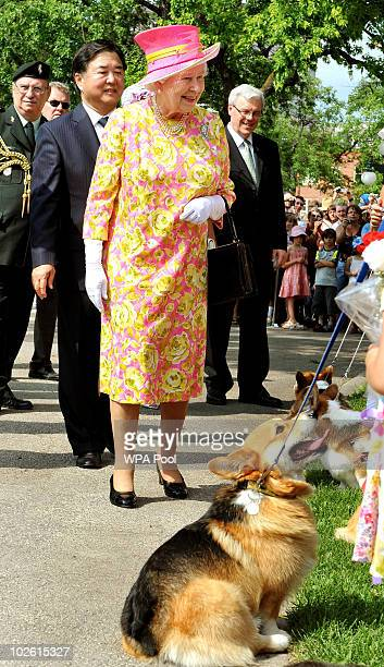 Queen Elizabeth II chats to corgi dogowners as she leaves Government House where she unveiled a statue of herself on July 3 2010 in Winnipeg Canada...