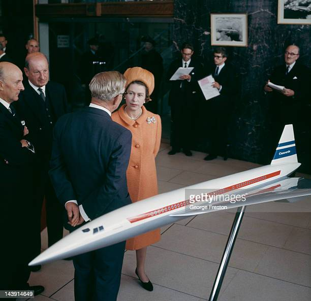 Queen Elizabeth II chatting with businessmen in front of a model of the Concorde airliner, at the British Aircraft Corporation works in Filton,...