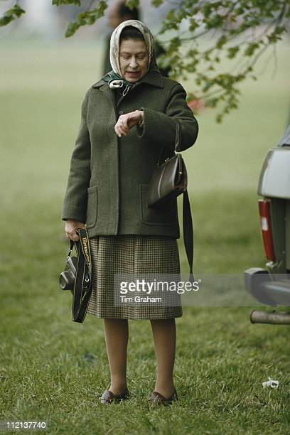 Queen Elizabeth II checking her watch at the Royal Windsor Horse Show held at Home Park in Windsor Berkshire England Great Britain circa 1985 The...