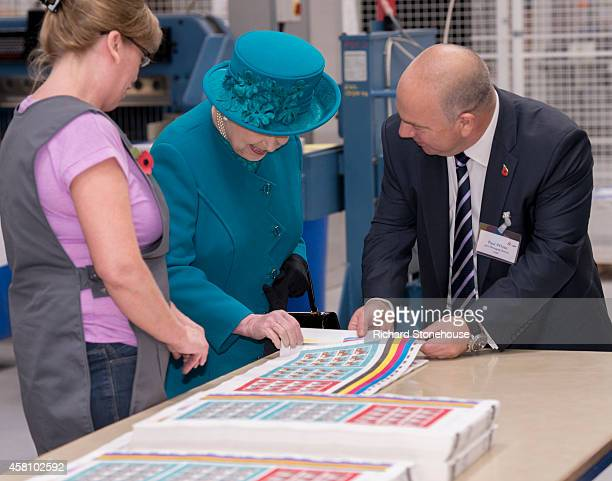 Queen Elizabeth II checks the quality control process with MD Paul White during an official visit to International Security Printers to view their...