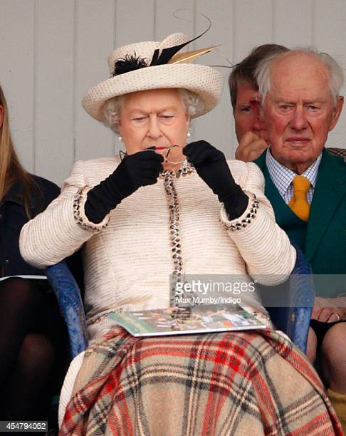 Queen Elizabeth II cleans her glasses as she attends the Braemar Gathering at the The Princess Royal and Duke of Fife Memorial Park on September 6...