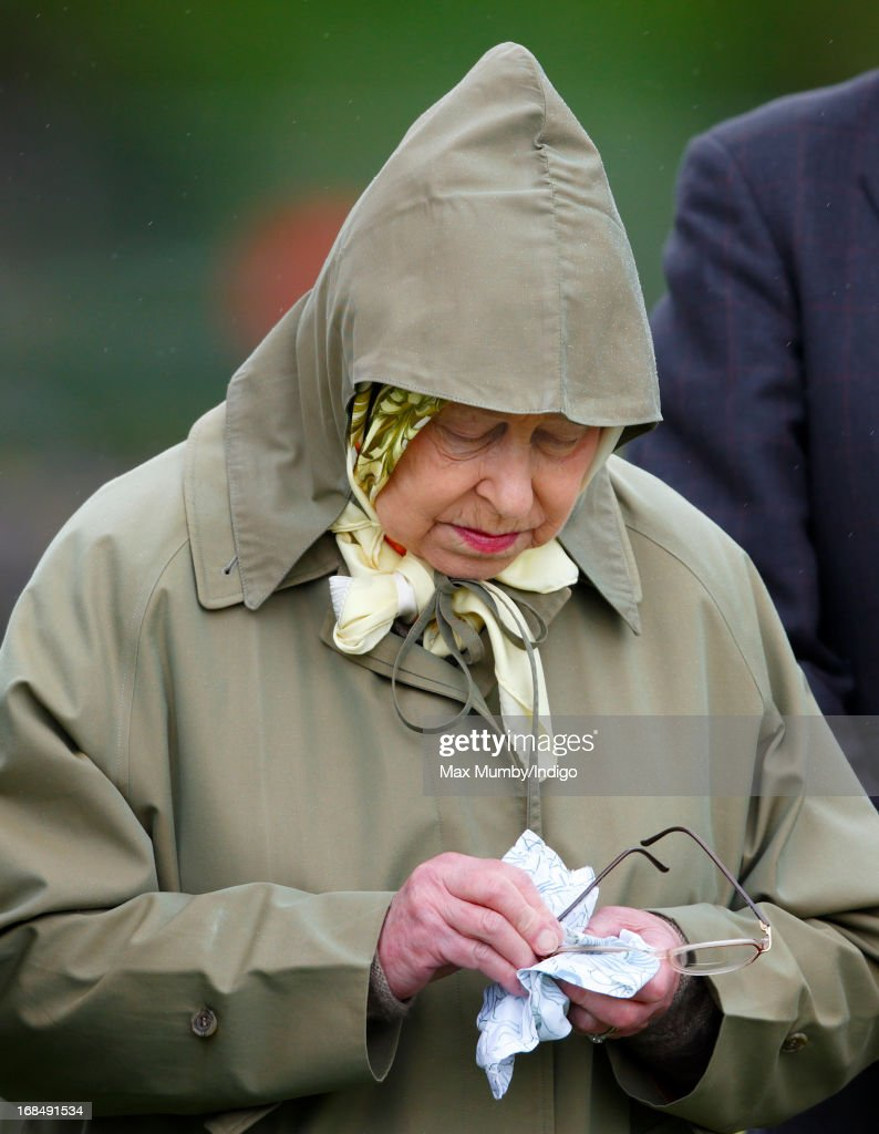 Queen Elizabeth II cleans her glasses as she watches one of her horses compete in the Highland class on day 3 of the Royal Windsor Horse Show on May 10, 2013 in Windsor, England.