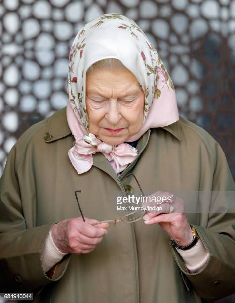 Queen Elizabeth II cleans her spectacles as she attends the Endurance event on day 3 of the Royal Windsor Horse Show in Windsor Great Park on May 12...
