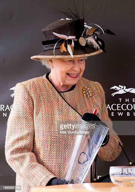 Queen Elizabeth II collects her trophy after her horse 'Sign Manual' won The Dreweatts Handicap Stakes at Newbury Racecourse on April 19 2013 in...