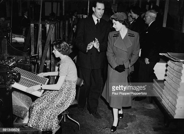 Queen Elizabeth II conducted by proprietor Horace Harrison, watches a girl operate a stamp machine during a tour of Harrison and Son Printing Works,...
