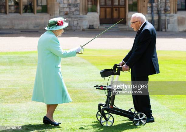 Queen Elizabeth II confers the Honour of Knighthood on Captain Sir Thomas Moore before presenting him with the insignia of Knight Bachelor during an...