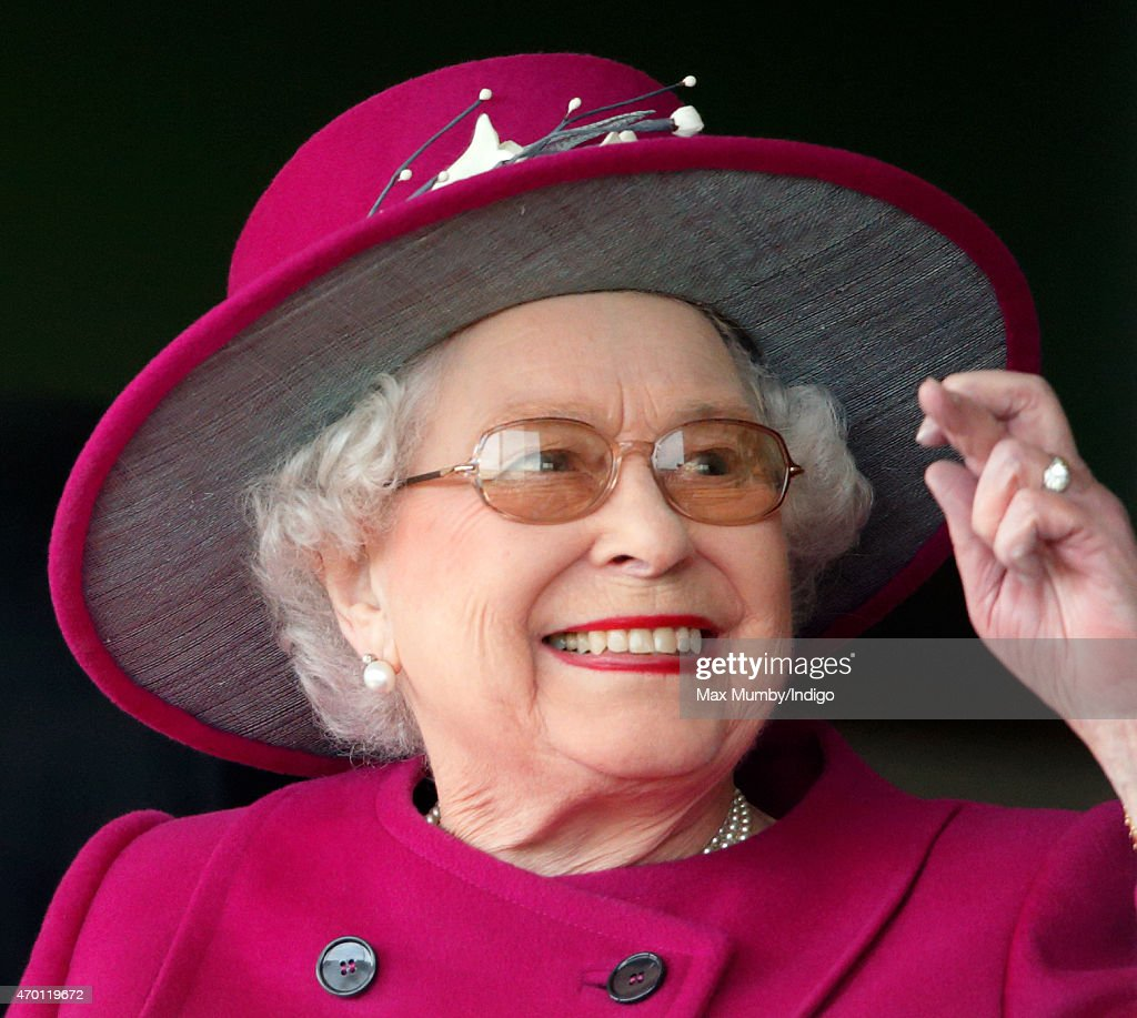Queen Elizabeth II crosses her fingers as she watches her horse 'Ring of Truth' run in the Al Basti Equiworld EBF Stallions Maiden Stakes during the Dubai Duty Free Spring Trials Meeting at Newbury Racecourse on April 17, 2015 in Newbury, England.