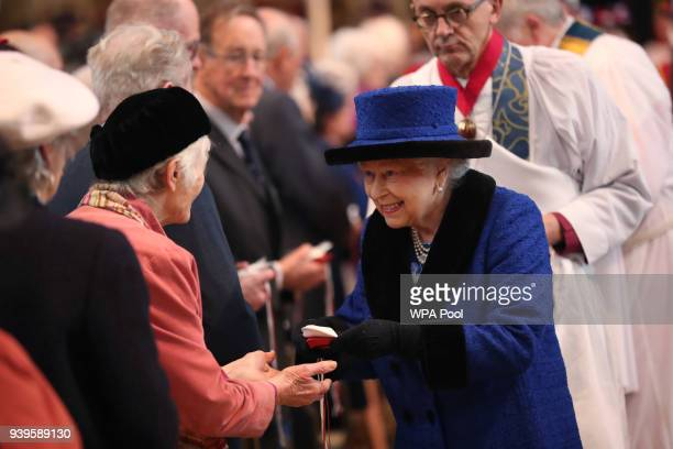 Queen Elizabeth II distributes the traditional Maundy money during the Royal Maundy service at St George's Chapel on March 29 2018 in Windsor England...
