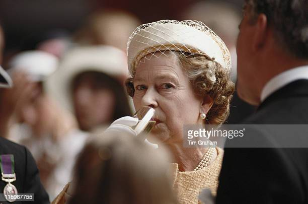 Queen Elizabeth II drinking a glass of champagne onboard HMS Invincible following a recommissioning service in Portsmouth Hampshire England Great...