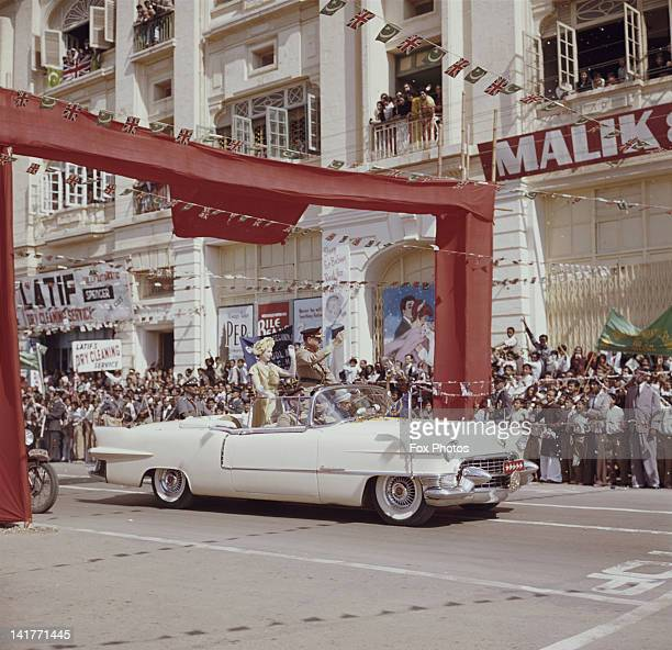Queen Elizabeth II drives through Karachi in a white Cadillac at the start of her visit to Pakistan 1st February 1961 She is accompanied by Pakistani...